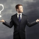 businessman holding exclamation and question mark