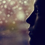 Woman looking out of rainy window